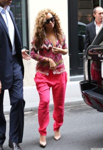 Beyonce in a hot pink and yellow zigzag print blouse, pointy high heels and hot pink pants.